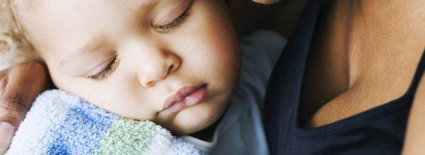 Bébé endormi dans les bras de Maman