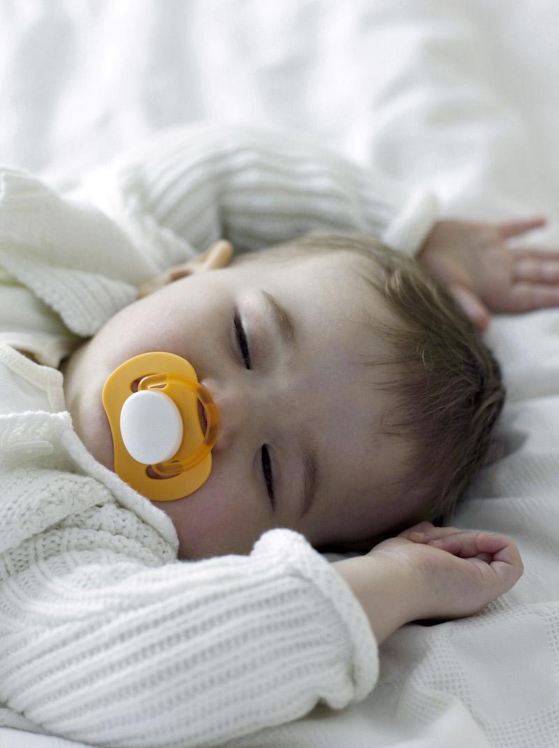 Enfant dormant la tétine à la bouche