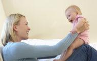 Bébé souriant sur les genoux de maman
