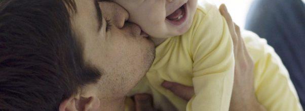 Bébé souriant dans les bras de papa